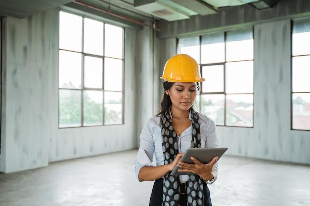 De vrouweningenieur die bouwvakker dragen houdt een digitale tablet