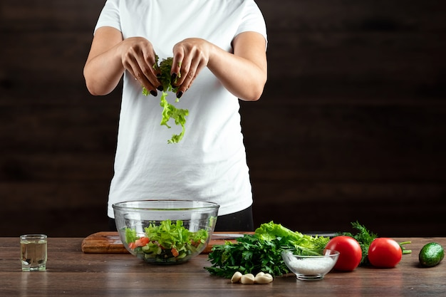 De vrouwenkok snijdt groenten voor saladevoorbereiding op hout.