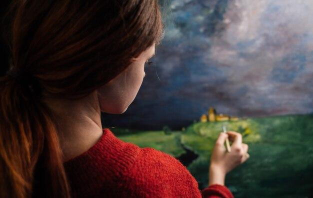 De vrouwenkunstenaar schildert een beeld met een borstel onn schildersezel