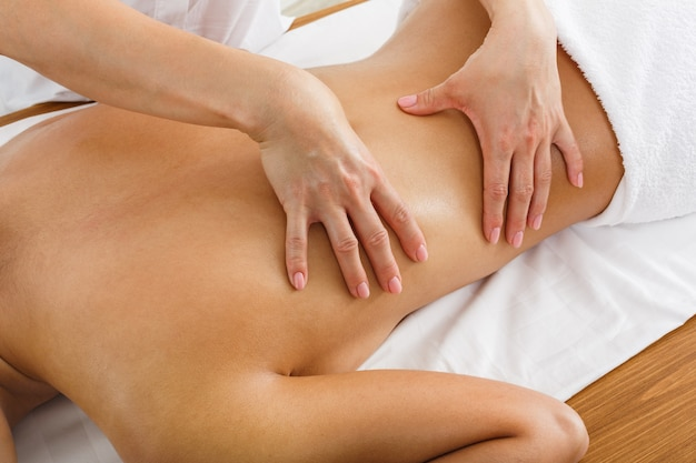 De vrouwenmassagist maakt lichaamsmassage in het wellnesscentrum van het kuuroord