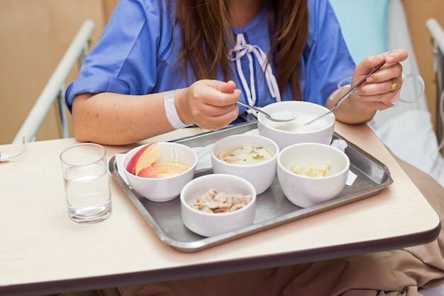 De vrouwenpatiënt zit op bed in het ziekenhuisruimte etend voedsel