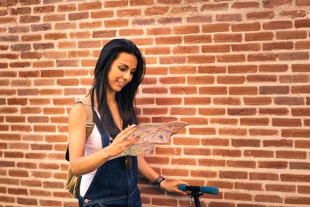 De vrouwentoerist die van jeans in een kaart kijkt
