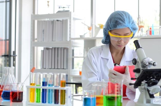 De vrouwenwetenschapper in laboratorium die experimenten met chemische vloeistof doen en controlelijst doen
