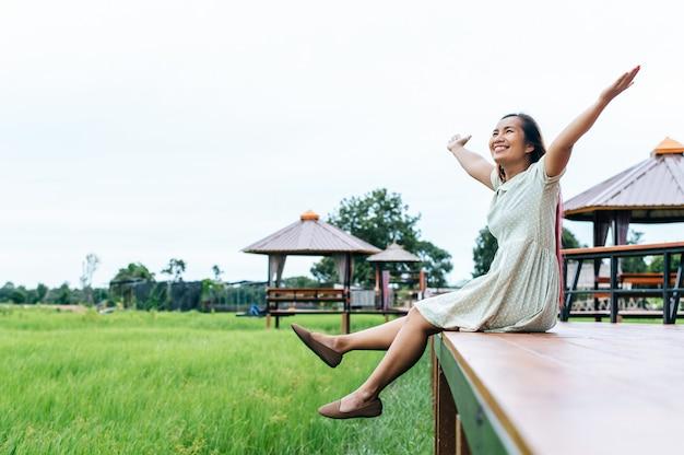 De vrouwenzitting en ontspant op houten brug met hun benen die neer hangen