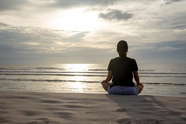 De vrouwenzitting in meditatie stelt op het strand in de ochtend.