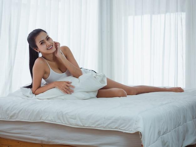 De vrouwenzitting stelt op een wit bed, ontspant tijd