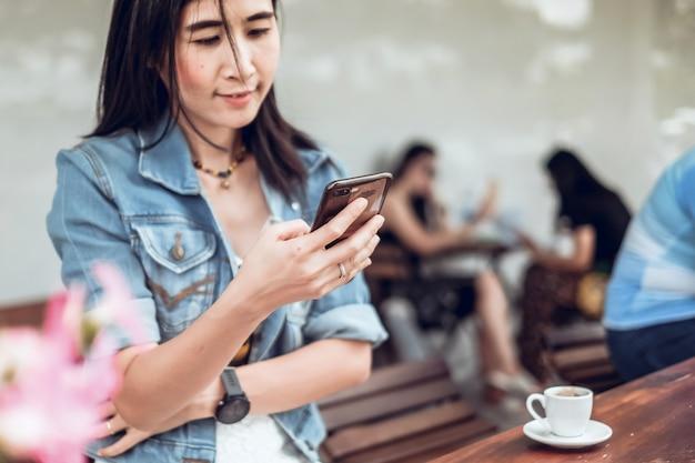 De vrouwenzitting van azië in de koffiewinkel en het gebruiken van mobiele telefoon