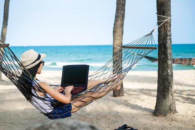 De vrouwenzitting van azië op de hangmat dichtbij het strand en het gebruiken van laptop voor haar werk en het controleren van zaken tijdens haar vakantie.