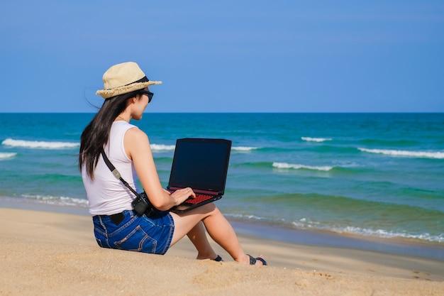 De vrouwenzitting van azië op het strand en het gebruiken van laptop voor haar werk en het controleren van zaken tijdens haar vakantie.