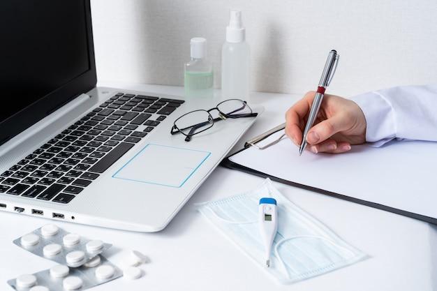 De vrouwenzitting van de arts bij het bureau met computer op werkplaats in het ziekenhuisbureau