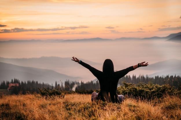 De vrouwenzitting van de yoga bovenop een berg bij zonsopgang.