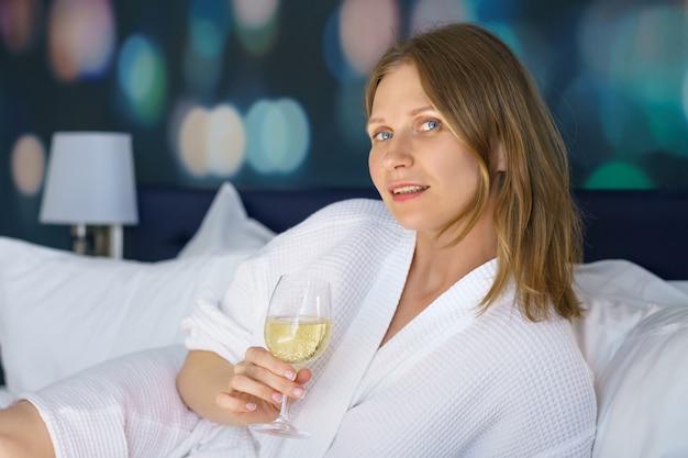 De vrouwenzitting van nice in bed met een glas wijn thuis