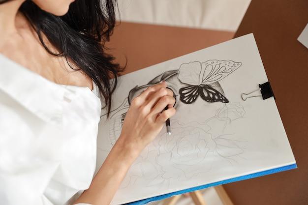 De vrouwkunstenaar dient de witte afbeelding van de overhemdstekening met potlood in (het concept van de vrouwenlevensstijl)