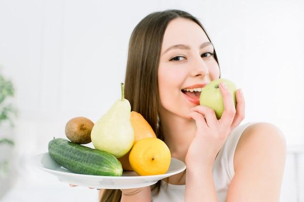 De vruchten van de vrouwenholding assortiment op witte plaat tegen lichte achtergrond wordt gediend die. close-upportret van vrolijke jonge vrouw die met perfecte tanden groene appel bijten. gezond, schoonheidsconcept