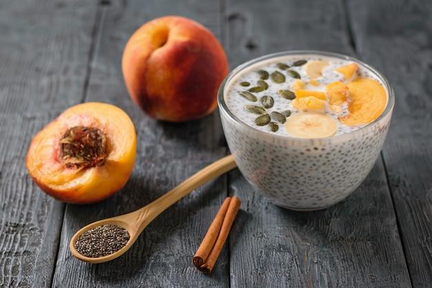 De vruchten van perzik en pudding van chia zaden zwart op zwarte rustieke tafel.