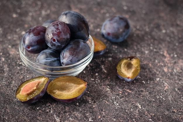 De vruchten van rijpe blauwe pruimen in een glazen kom op de stenen tafel.