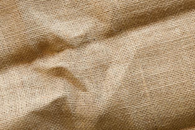 De vuile achtergrond van de jutetextuur, bruine katoenen stoffentextuur, canvas