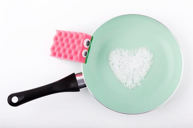 De vuile vaat schoonmaken met een roze spons met afwasmiddel.