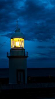 De vuurtoren die bij donkere nacht op kust spanje gloeit