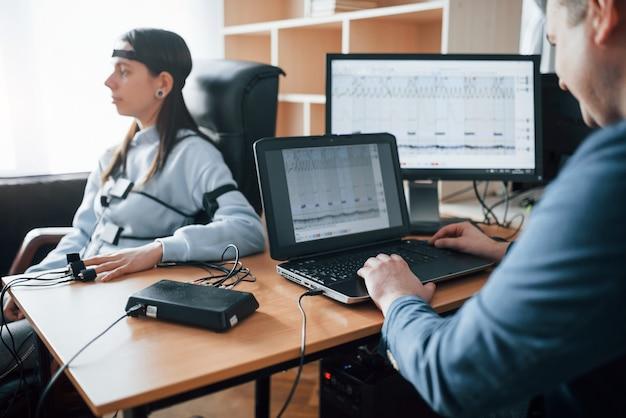 De waarheid controleren. meisje passeert leugendetector in het kantoor. vragen stellen. polygraaftest