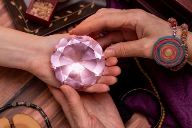 De waarzegster van de vrouw legt een bal van het lot in haar hand, een magische bal van voorspellingen. concept van het voorspellen van de toekomst, magie, occultisme.