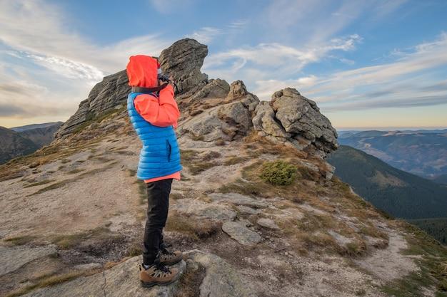 De wandelaar die van de jong kindjongen beelden in bergen nemen