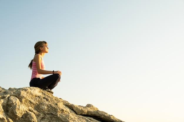 De wandelaarzitting van de vrouw op een steile grote rots die van warme de zomerdag geniet. jonge vrouwelijke klimmer die tijdens sportactiviteit in aard rust. actieve recreatie in de natuur concept.