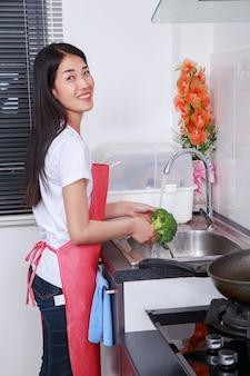 De was van de vrouw broccoli onder lopend water bij de keukengootsteen