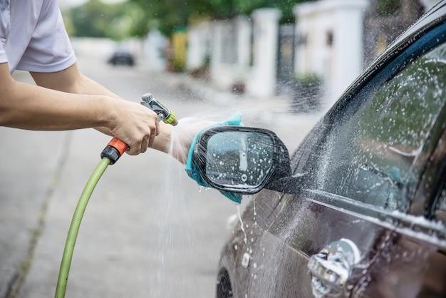 De wasauto van de mens gebruikend nevelstraalwater