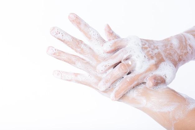De washanden van de close-upvrouw met zeep op witte achtergrond