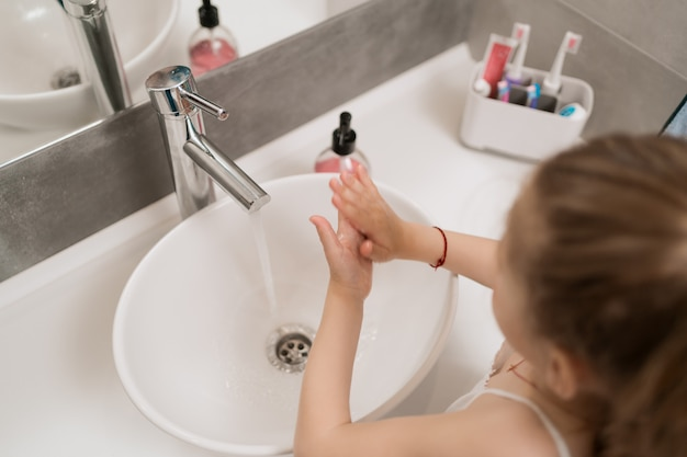 De washanden van het meisje met zeep