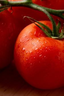 De waterdalingen o tomatengroenten op houten plaat sluiten omhoog, macro