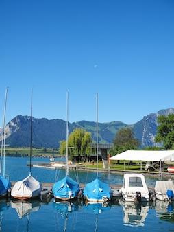 De waterkant van thun in zwitserland met jachten op een zonnige zomerochtend