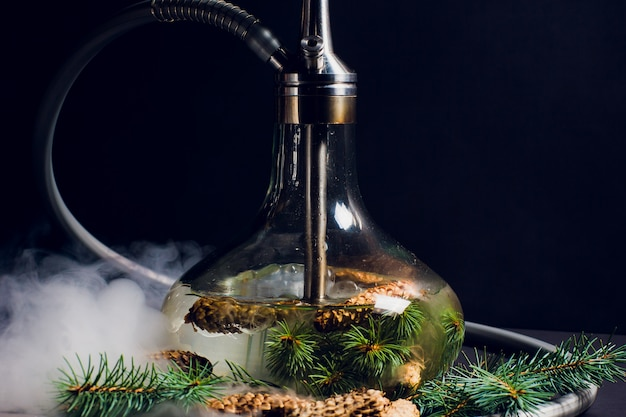 De waterpijp van het nieuwe jaar, de geur van de waterpijp, er zijn kegels en takken van de boom in de buurt