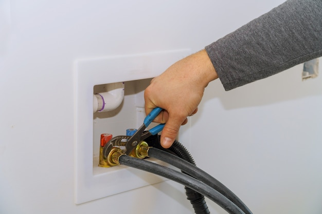 De watertoevoerslang op de wasmachine aansluiten met een sleutel