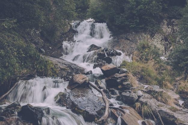 De watervalscène van de close-upmening in bergen, nationaal park van dombay, kaukasus, rusland. zomerlandschap, zonnig weer en zonnige dag
