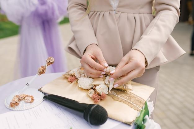 De weddingplanner legt de trouwringen op het kussen. de ceremonie van het huwelijk