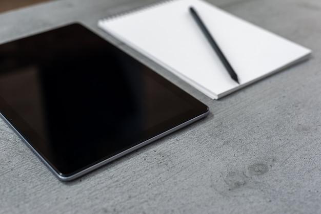De weergave van een deel van een grijs bureaublad met uitzicht op een tablet en een notitieboekje met een potlood.