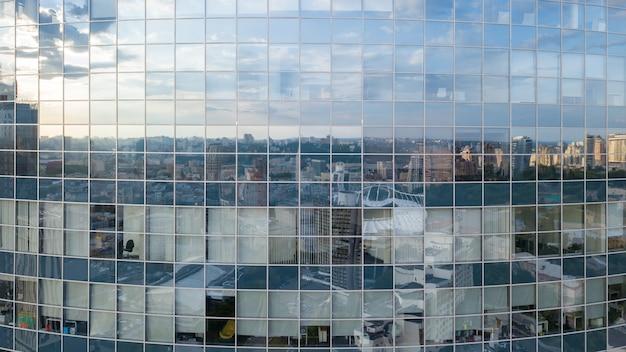 De weerspiegeling van stadsgezicht in de ramen van het moderne zakencentrum bouwen in de zomerdag, bij zonsondergang.