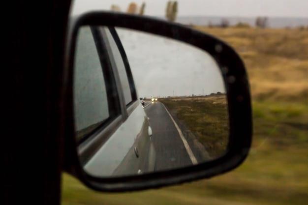 De weerspiegeling van weg in de zijaanzichtspiegel met regendruppels. reizen concept.