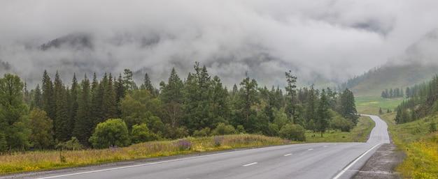 De weg gaat door een bergdal, regenachtig weer