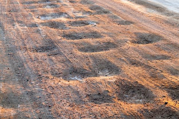 De weg in het winterseizoen, de rijbaan is na het schoonmaken bedekt met gesmolten sneeuw en een groot aantal auto's die er doorheen reden