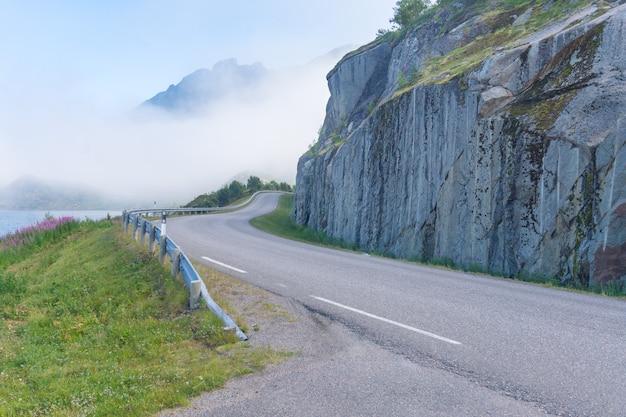 De weg is gebogen rond de klif tegen de bergen, noorwegen