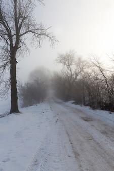 De weg is gevaarlijk en glad na kou en vorst, een weg bedekt met sneeuw in het winterseizoen
