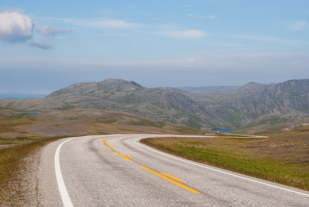 De weg is ver weg tegen de achtergrond van steenachtige heuvels