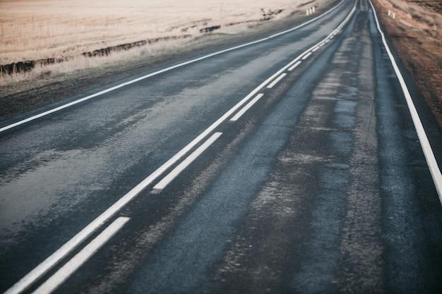 De weg na de regen tussen de velden.