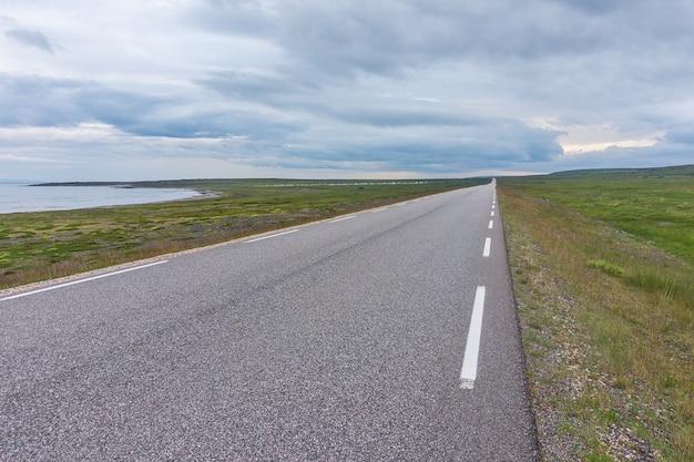 De weg strekt zich uit in de verte op een achtergrond van groene weiden