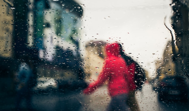 De weg van de stad die door regendalingen wordt gezien op het autowindscherm