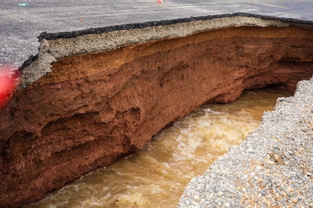 De weg werd verwoest door watererosie veroorzaakt door hevige regenval en overstromingen van de weg.