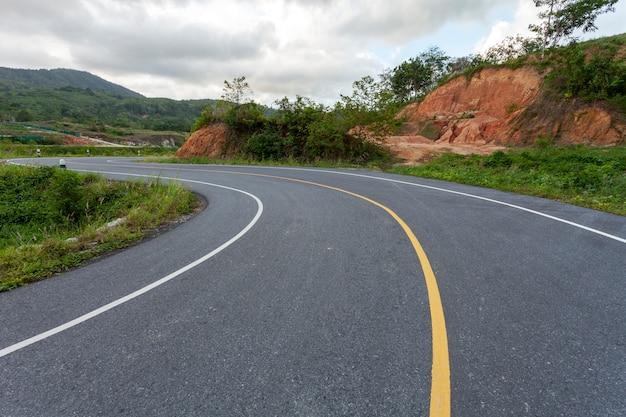 De wegkromme van het asfalt op de berg in slechte weerdag